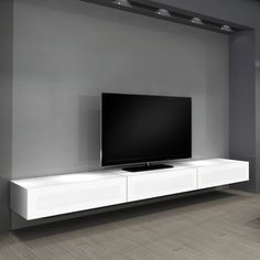 White Wooden Floating Media Shelves With Three Drawers And Black Led Tv On Grey Wall