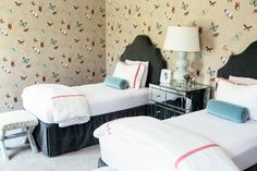 Shared girls' bedroom features walls clad in Nina Campbell FarFalla Butterfly Wallpaper lined with a pair of gray linen headboards on twin beds dressed in white and pink bedding as well as a blue velvet bolster pillow flanking a mirrored nightstands and a pale blue triple gourd lamp, Robert Abbey Triple Gourd Lucite Table Lamp.