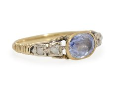 18th C. Sapphire Diamond Ring Exceptional. The estimated 1.5 carat gem has a delightfully distinct and ethereal pale blue coloration and is foiled and set closed back in 15k yellow gold. Each shoulder is appointed with an open work bridge and arched design set with a pair of rose cut diamonds (four in all with an estimated total weight of .12 carats) set in silver. Vertical bands along the sides add textural and visual interest to an unadorned smooth silken shank.  Date: Circa 1750 - 1770.