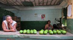 Un trabajador de un pequeño comercio agrario del gobierno totalitario cubano ofrece sus productos.
