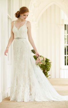 A combination of lace, tulle and satin, this wedding dress from Martina Liana features a lace illusion back that zips up under fabric covered buttons. The detachable beaded belt slims the waist, while the double layer skirt adds interesting detail.