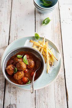 Gezonde frietjes van pastinaak met peterseliegehaktballetjes  Voor 2 personen:  300g kalfsgehakt, 1 rode ui (fijngesnipperd), 2 teentjes knoflook 1 handvol peterselie (fijngehakt), zwarte peper en snuifje zeezout, olijfolie, 2 wortelen (in kleine stukjes), 600g tomatenblokjes (vers of uit blik), 1 el tomatenpuree, Provençaalse kruiden, 2 pastinaken (geschild en in frietjes), gedroogde tijm, basilicum