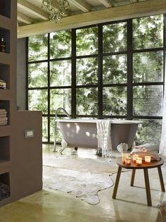 Rå materialer mot glassveggen, som viser hagen bakenfor. Vindusveggen er laget av den lokale smeden – alle vinduene i hele huset er laget i jern. Badekaret er fra en antikvitetsbutikk i Amsterdam, malt flere ganger i ulike farger. (Foto: Per Erik Jæger)