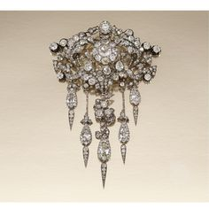 DIAMOND DEVANT DE CORSAGE, 1860s, of foliate design, centering on a diamond cluster within an open work surround of acanthus and ivy leaves, suspending five articulated pendant drops, set with cushion-, pear-shaped, circular- and rose-cut diamonds, further embellished with cushion-shaped and circular-cut stones in cut-down collets, later brooch fitting, original fitted case.