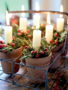 Rustic Christmas centerpiece with a milk crate, small terra cotta pots, greenery, and candles.