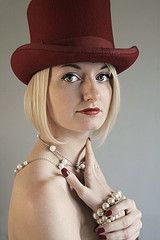 Woman in red top hat and pearls.