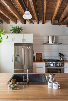 This eco-friendly Philly loft was once a pickle factory! The kitchen has unfinished wood ceilings white walls tiles and cabinets stainless steel kitchen appliances and wood countertops. Kitchen Tiles Design, Kitchen Wall Tiles, Tile Design, Kitchen Backsplash, New Kitchen, Kitchen Decor, Kitchen Wood, Kitchen Modern, Kitchen Ideas