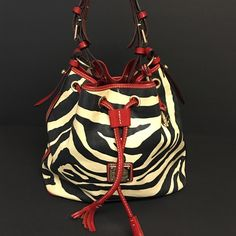 Auth. Dooney & Bourke Bucket Drawstring Zebra Red Adorable Dooney and Bourke shoulder bag drawstring bag. Zebra with red trimming. Great condition with wear on edges of the bottom of the bag. Interior has small stains. Dooney & Bourke Bags Shoulder Bags