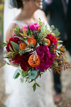 Bridal bouquet comprised of vibrant jewel-toned flowers, berries and eucalyptus. Petalworks.