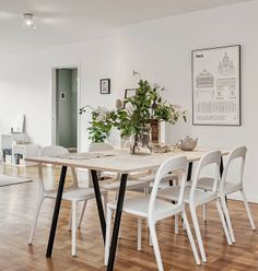a paris architecture print, birch table, and simple sculptured chairs with an abundance of greenery