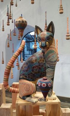 Artista Jacobo Angeles. Oaxaca, México: this cat must be HUGE because those are molinillos (Mexican hand-carved hot cocoa frothers often 14 inches long) hanging around it!!