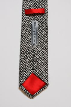 The Noir Silk Tweed Necktie is remarkable. Made from handwoven silk tweed, it has amazing texture. Inspired by Italian mens fashion, it blends classic elegance with modern sophistication. The red silk satin tipping accentuates this tie's depth of character.