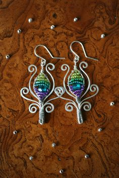 Wire wrap and beaded peacock feather earrings by ErinMalaspino