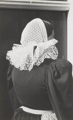 Vrouw in streekdracht uit Huizen. Ze is gekleed in de daagse dracht. Op het hoofd draagt ze een 'pikmuts' (gehaakte muts). Deze mutsen worden gedragen door vrouwen, die zondags een cornetmuts dragen.