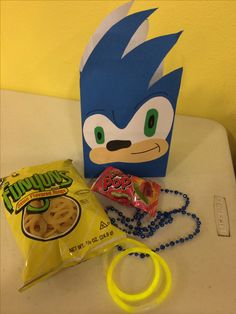 Treats for Sonic the Hedgehog party. Blue necklace, Funyuns and yellow glow bracelets to resemble the rings sonic must collect, and a ring pop to resemble the master chaos emerald.