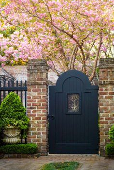 black pickets, black gate, brick gate posts, traditional boxwood mini hedges and urn