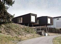 This black wooden house in Austria by Hammerschmid Pachl Seebacher Architekten is raised off the ground on wonky metal stilts to frame views of the landscape and allow room underneath for a sheltered garden