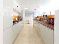 Orange, white and brown tea point and kitchenette area. Designed by Interaction for Parmenion, an office based in Bristol, UK.