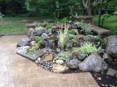 landscape design waterfalls water feature paver patio sitting wall with pillars, outdoor living, patio, ponds water features, Pondless Waterfall with Low Voltage Lighting and Rock Garden by Acorn Landscaping in Brighton NY Boulder Fountain with Waterfalls