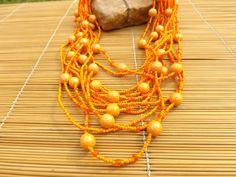 colar de miçangas e bolas de resina todas em tons de laranja o acabamento em ouro velho.