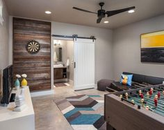 Designer Jordan Iverson mixes contemporary furniture with rustic accents and industrial finishes to turn this pool house into a party-ready game room that can also host overnight guests.