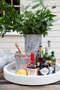 Love this round tray with straight sides. Also the combo of ceramics and the metal buckets and the fresh leaves. Great look and still very inviting.