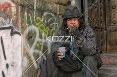 mid adult man wearing hat and smoking against graffiti wall. - Image of a mid white adult male smoking against graffiti wall, and sitting on the steps of a building in lower manhattan, Place: New York City, USA