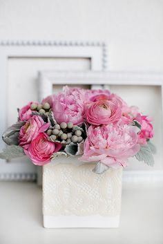 Pink ranaculus and peonis paired with grey hued greeneries in a white vase