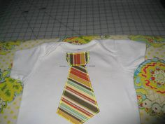 """MaterialsBaby bodysuit or teeTie pattern (see link to pdf at end of this post)Fabric scrap for tie - you could get away with as little as 4"""" X 8"""" or 5"""" X 6"""" if you're cutting the tail piece at an a..."""
