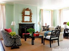 """For the living room of a traditional New York apartment, designer Todd Klein chose a light, cool green. """"If you think of a house as having seasons, the living room is spring,"""" Klein says. Graphic black-and-white fabrics from China Seas—Macoco Reverse on the sofa and Potalla Background on the pillow—""""add a touch of youthfulness and whimsy."""" Walls are Vreeland Mint and trim is White, both in Brilliant, by Fine Paints of Europe."""
