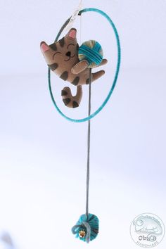 Handmade felt mobile with cat and wool ball.