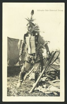 This shows an unidentified Lakota man at a Pow Wow. He is dressed in traditional clothing of the tribe, including head piece, feathers and a bone breast place. There are several bells strapped to his clothing. A tipi is seen to the right, at his feet, with supplies stacked on the ground. In the background can be seen another tent. Date	circa 1920