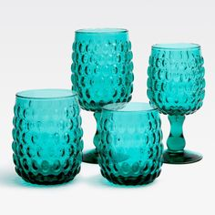 Oval-shaped beads on the Claire's surface make this set as unique as it is versatile. The clear glassware can be part of any setting; or introduce jewel tones to your table with vibrant teal.  Finish: Teal Material: Hand Blown Glass
