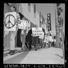 """Title:Marchers with signs reading """"Have A Dream"""", """"We Mourn Dr King"""" and the peace symbol walking down sidewalk in Van Nuys, Calif., 1968  Publication:Los Angeles Times  Publication date:April 7, 1968"""