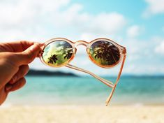 palm trees reflected in round sunglasses