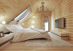 Log home attic master bedroom with wood walls and ceiling. Skylights bring in natural light.