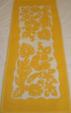 Hawaiian quilt table runner 100% hand quilted/hand appliqued Hawaiiana by Hawaiian Quilts & Gifts. $59.95. 100% Brand New Hawaiian Handmade Table Runner / Wall Hanging 20x50. It has 3 loops in the back where you can insert a rod for easy hanging. 100% Hand Quilted and 100% Hand Appliqued. There's a count of 6-8 stitches in an inch. Yellow HIbiscus Design. ALOHA, this quilt is made of 65% Polyester and 35% Cotton.  Which makes the quilt 100% machine washable.  We hand...