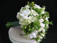 White hydrangea is the base for this beautiful bouquet also featuring white freesia, green hypericum and pieces of bells of ireland