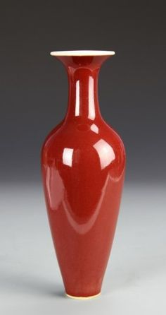 China, 19th C., oxblood glazed vase with tapering form, long neck and flared lip, smooth high polish finish, white glaze on bottom, rim, and interior, double ring mark on base. Height 9 in.