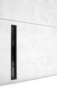 Concrete wall with narrow window.