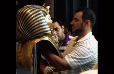 """In this Aug. 12, 2014, photo provided by Jacqueline Rodriguez, a man glues the beard part of King Tutankhamun's mask back on at the Egyptian Museum in Cairo, Egypt."" (ahram.org)"
