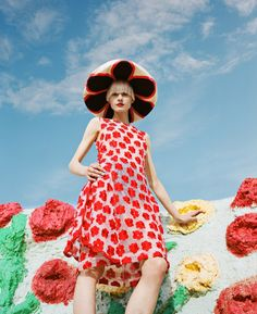 This dramatic shot features model Nora posing at the famous art installation in a red, spot adorned dress