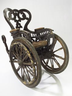 Invalid chair, Europe, 1850-1890:Unlike modern wheelchairs that have four wheels, this chair has three: two large front wheels and one small rear wheel. This means the patient was unable to wheel the chair themselves. They would have had an assistant. The chair is heavy so presumably they would not have gone very far or very fast. This elaborately carved chair dates from the late 1800s. It is made of wood with a sprung padded seat. It was donated to the Wellcome Collec