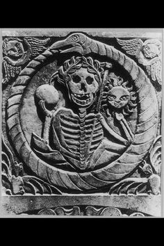 Headstone featuring Death, crowned with a wreath and holding sun and moon, surrounded by Ouroboros, angels/putti, and bats.