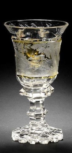 A Bohemian part amber stained goblet, dated 1841 The campana shaped bowl in clear glass with only the square panel stained in amber, engraved with a stag hunting scene, a running stag surrounded by a pack of hounds, the flared rim engraved with the inscription '25 Jarige vereeniging van C. van Opstall en J.J. Rom 6 December Ao 1841', on a clear glass octagonal knopped stem and scalloped foot cut with an intricate diaper pattern on the underside, 21.7cm high