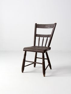late 1800s This is an antique primitive wood chair in a thick sheraton style. The chair features two back rails with spindles. The tone of the paint is a deep, near black, brown. - primitive wood chai