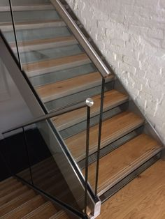 Frameless glass balustrade with stainless steel slotted channel tube top rail on new steel staircase