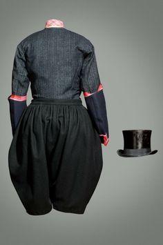 """Kostuum van Marker bruidegom, 1900 Huwelijk 8 hoogtepunten, waaraan kostuum telkens werd aangepast. Op belangrijkste dag droeg bruidegom wit linnen bruidegomshemd met rood wollen hemd (""""trouwwollen""""hemd) en zwart sarris (wol) bruidegomsrokkie. Over onderbroek droeg hij zwart sarris bruidegomsbroek, met blauw gebreide kousen en zwart leren bruidegomsschoenen; zwarte hoge hoed. Omdat dit minst aan slijtage onderhevig was, waarschijnlijk oudste overgeleverde dracht. #NoordHolland #Marken"""