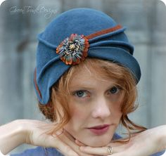 Blue Flapper Cloche Hat - A Hand Sculpted Felt Hat by Green Trunk Designs I made this enchanting cloche hat from a dark cornflower blue millinery fur felt. Using free-form blocking techniques I hand sculpted the felt into a unique and glamorous 1920s style cloche hat. The hat is embellished with a band of copper brown felt and a pheasant feather flower that was made especially for Green Trunk Designs by a family friend. The inside of hat is lined in brown taffeta and has a burnt orange ...