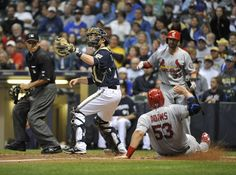 Matt Adams slides home safely as Jonathan Lucroy of the Milwaukee Brewers waits for the throw during the eighth inning.  Cards won the game 7-2.  9-21-13